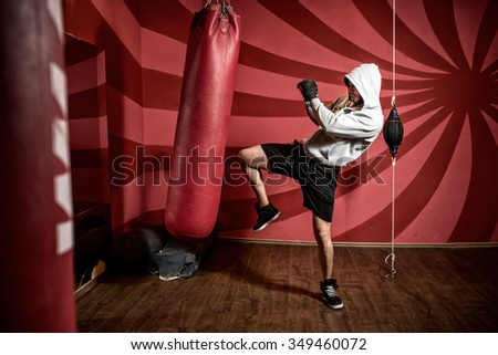 Boxer and athlete training and practicing kicks in the gym - stock photo