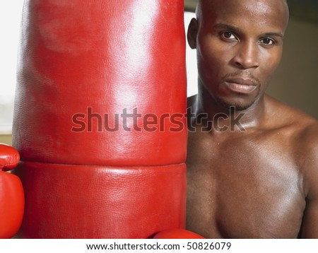 Boxer holding punching bag, portrait, close-up - stock photo