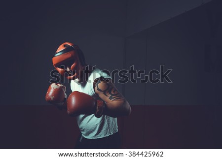 Boxer in helmet on a dark background, where the face is not visible. Male boxer in red helmet and gloves. Sports man boxing. Training. Fighter, warrior, fighting without rules.  Toned image.