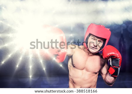 Boxer punching against black background against red boxing area with punching bags - stock photo