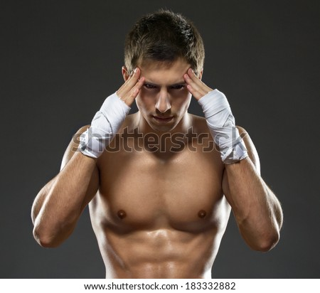 Boxer puts his wrapped with elastic bandage hands on head, isolated on black - stock photo