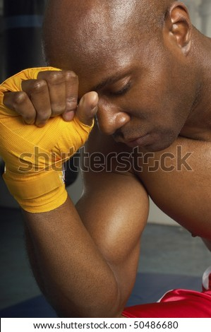 Boxer with head on wrapped hand, head and shoulders - stock photo