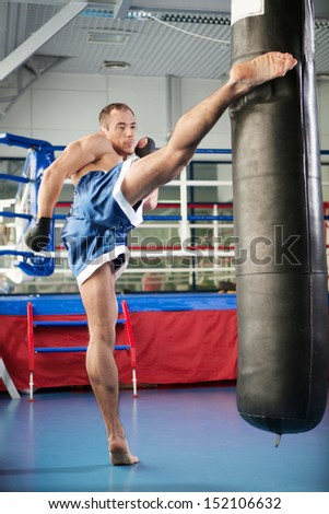 Boxer. Young confident kickboxer training at the punching bag - stock photo