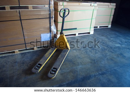 Boxes and pallet truck in the old warehouse - stock photo
