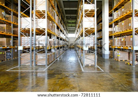 Boxes in modern logistic distribution warehouse interior - stock photo