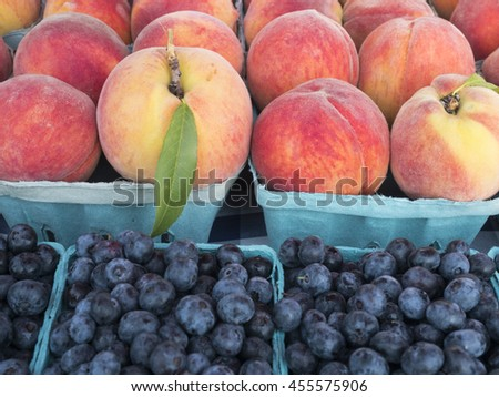 Boxes of fresh peaches and blueberries at farm market. - stock photo
