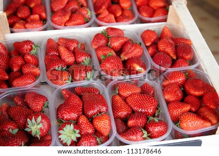Boxes of fresh strawberries displayed for sale - stock photo