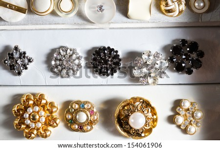 Boxes of precious, jewel-like vintage buttons stacked in rows in a haberdashery. - stock photo