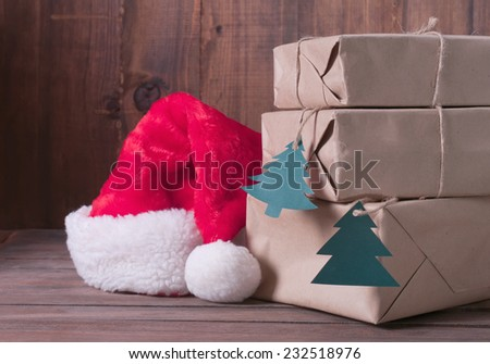 boxes with Christmas presents and santa hat on a wooden background - stock photo