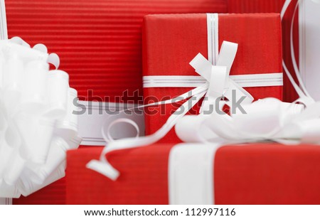 Boxes with presents wrapped in red paper and white bows, close up - stock photo
