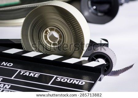 Boxes with the camera films and cinema clapper on the table. Movie industry - stock photo