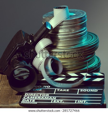 Boxes with the camera films and film clapper lie on the board. - stock photo