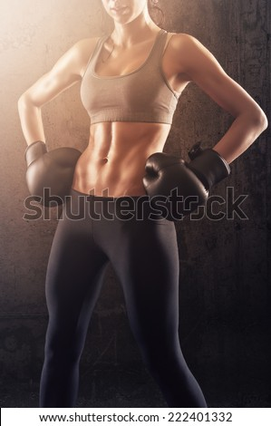 Boxing girl showing her strength and muscles - stock photo