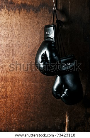 Boxing glove hanging on wooden background