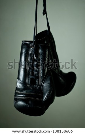 Boxing gloves hanging from laces on a grey background - stock photo