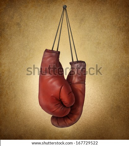 Boxing gloves hanging on an old vintage grunge background with laces nailed to a wall as a business or sport concept of retiring giving up the fight or preparing for competition. - stock photo