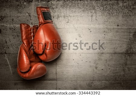 Boxing gloves hanging on concrete wall - stock photo