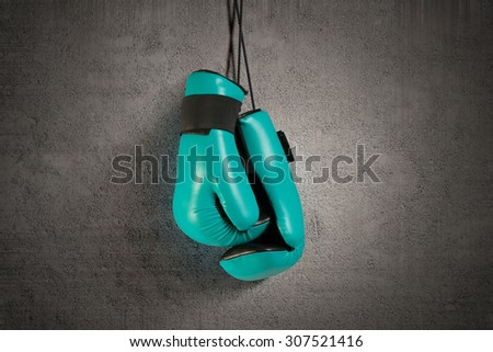 Boxing gloves hanging on nail on wall - stock photo