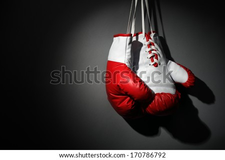 Boxing gloves hanging on wall low key gray background with copy space - stock photo