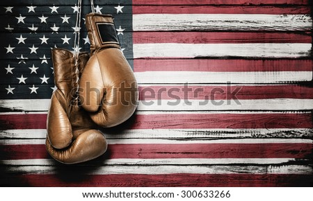 Boxing gloves hanging on wooden wall with American flag - stock photo