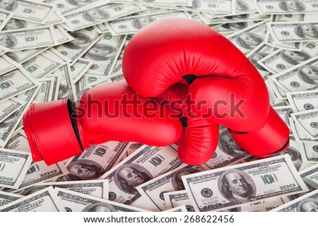 Boxing gloves on top of 100 dollars bills - stock photo