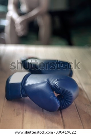 Boxing gloves on wood and young man sitting on background.