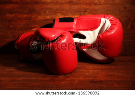 Boxing gloves on wooden background - stock photo