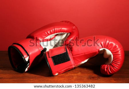 Boxing gloves on wooden table, on red background - stock photo