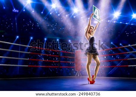 Boxing ring girl  is holding the number 4 - stock photo