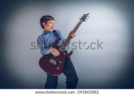 boy adolescence European appearance enthusiastically playing guitar cross process - stock photo