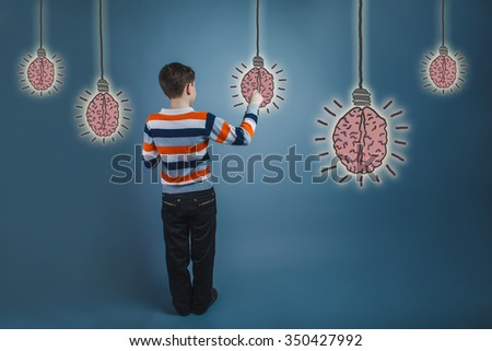 boy adolescent  view from the back draws brain bulb creative idea - stock photo