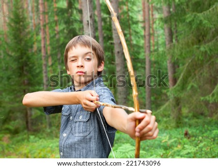 Boy aiming home-made wooden bow outdoors - stock photo