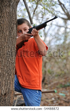 Boy aiming rifle - stock photo
