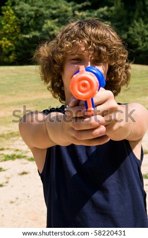 boy aiming water gun at you - stock photo