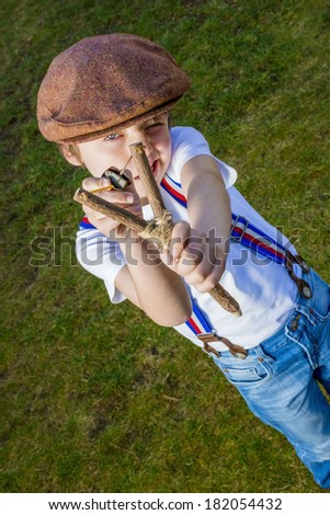 boy aiming with his slingshot - stock photo
