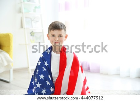 Boy and big American flag in room - stock photo