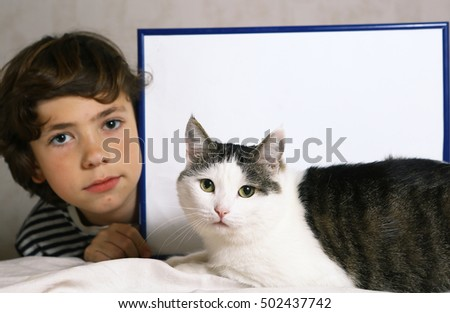 boy and cute cat with empty paper sheet in frame. Copy space in frame with boy and cat.