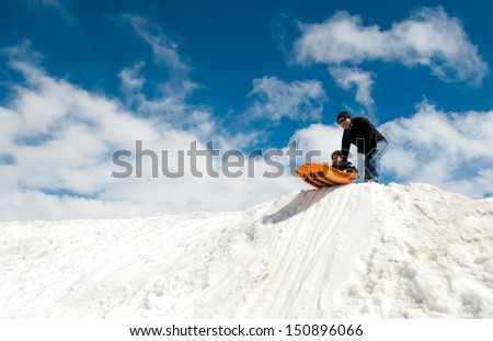 Boy and dad sledding in winter - stock photo