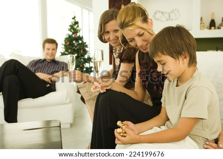 Boy and family sitting on couch, looking at Christmas ornament, Christmas tree in background - stock photo