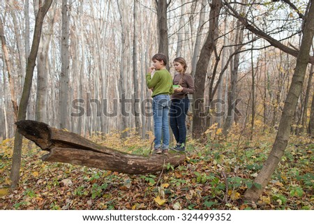 Boy and girl are eating sandwiches in autumn forest - stock photo