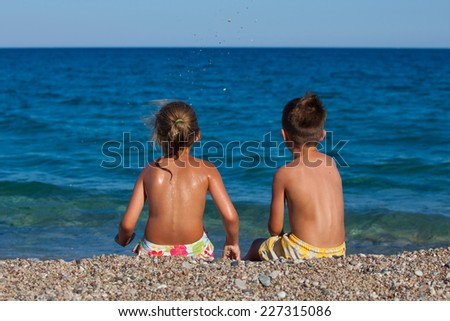 Boy and girl are sitting on the beach