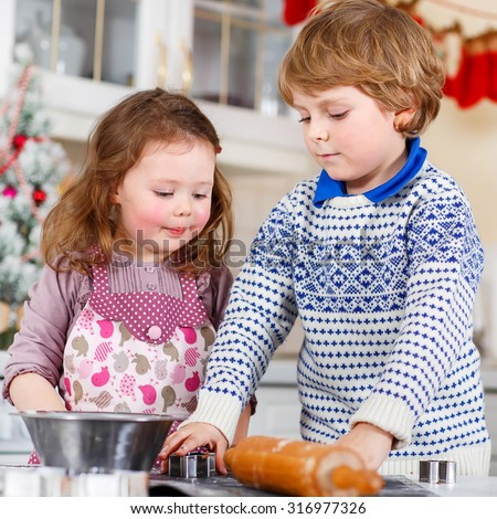 Boy and girl baking Christmas cookies at home. Siblings, brother and little sister having fun in domestic decorated kitchen. Traditional leisure with kids on Xmas - stock photo