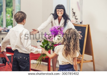 Boy and girl children give flowers as a school teacher in teacher's day - stock photo