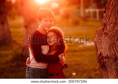 boy and girl children hugging at sunset summer romance in nature photos - stock photo