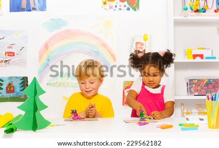 Boy and girl craft together forms of playing dough - stock photo