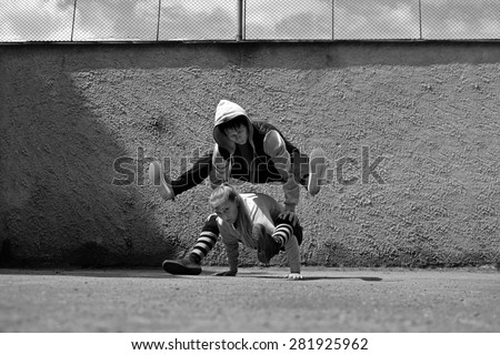 Boy and girl dancing break dance on the street - stock photo