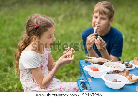 Boy and girl eat meat with vegetables at the picnic on pembroke table - stock photo