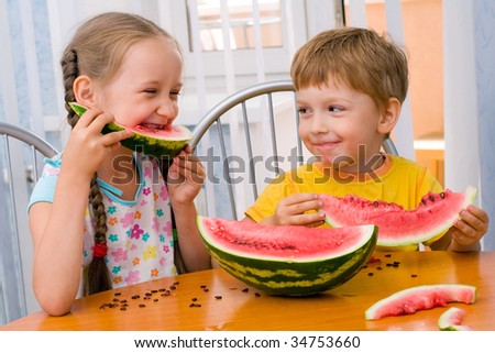 boy and girl eat ripe watermelon - stock photo