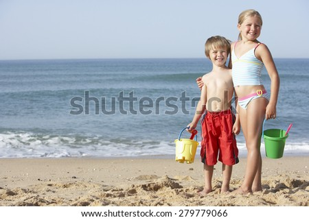 Boy And Girl Enjoying Beach Holiday - stock photo