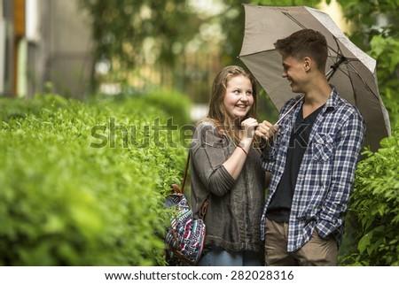Boy and girl having fun in the Park under an umbrella. - stock photo